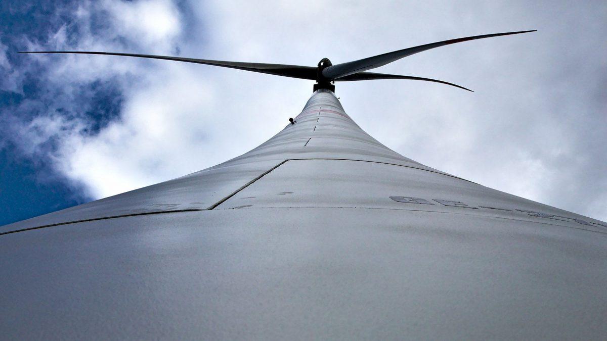 Windkraftanlage von unten mit blauem Himmel