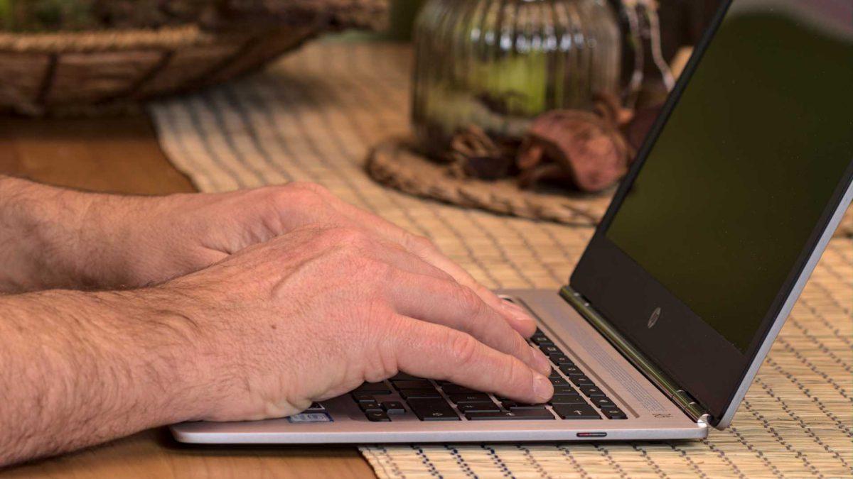 laptop mit händen auf tisch