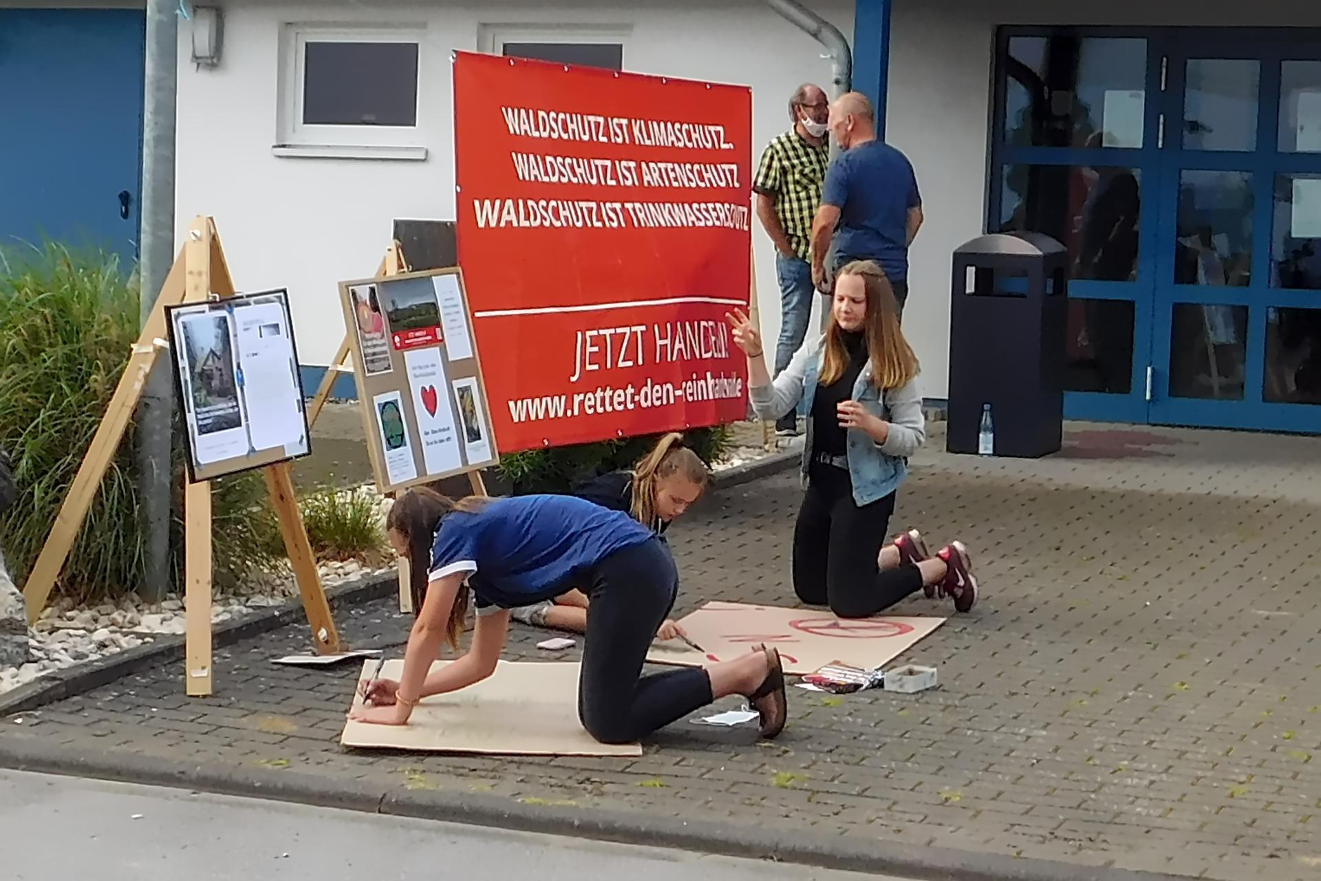 Jugendliche malen Plakate gegen den Windpark