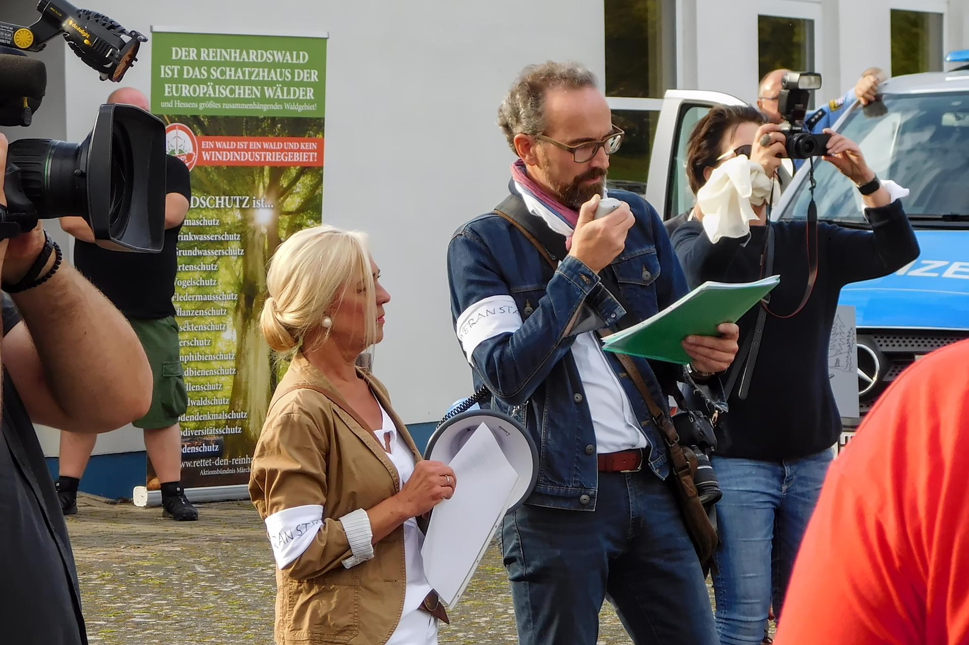 Sonja Erler und Karsten Leineke am Megaphone mit Presse im Hintergrund